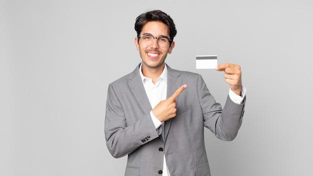 Jonge spaanse man die vrolijk lacht, zich gelukkig voelt en naar de zijkant wijst en een creditcard vasthoudt
