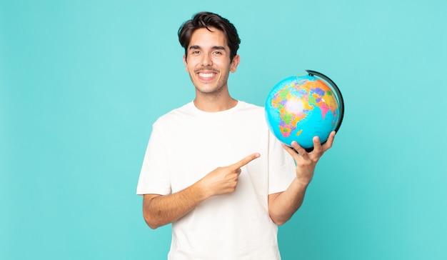 Jonge spaanse man die vrolijk lacht, zich gelukkig voelt en naar de zijkant wijst en een wereldbolkaart vasthoudt