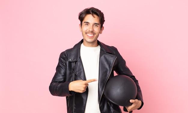 Jonge spaanse man die vrolijk lacht, zich gelukkig voelt en naar de zijkant wijst. motorrijder concept