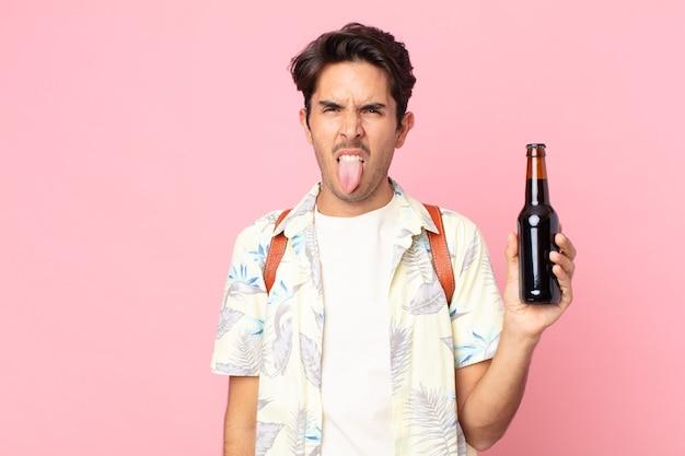 Jonge spaanse man die walgt en geïrriteerd voelt en zijn tong uitsteekt en een flesje bier vasthoudt