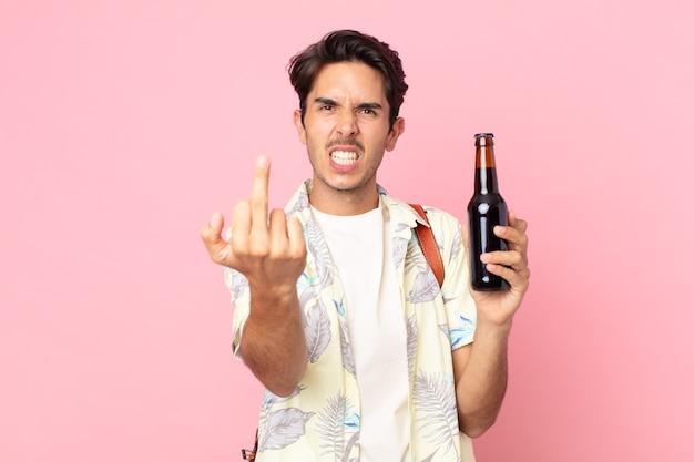 Jonge spaanse man die zich boos, geïrriteerd, opstandig en agressief voelt en een flesje bier vasthoudt