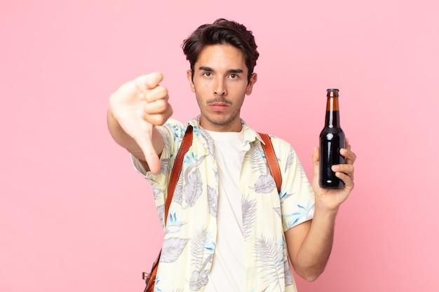 Jonge spaanse man die zich boos voelt, duimen naar beneden laat zien en een flesje bier vasthoudt