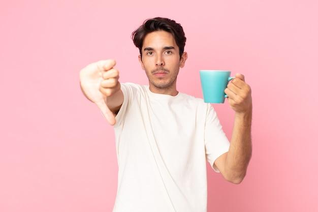 Jonge spaanse man die zich boos voelt, duimen naar beneden laat zien en een koffiemok vasthoudt