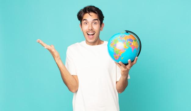Jonge spaanse man die zich gelukkig en verbaasd voelt over iets ongelooflijks en een wereldbolkaart vasthoudt