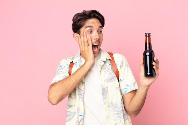 Jonge spaanse man die zich gelukkig, opgewonden en verrast voelt en een flesje bier vasthoudt