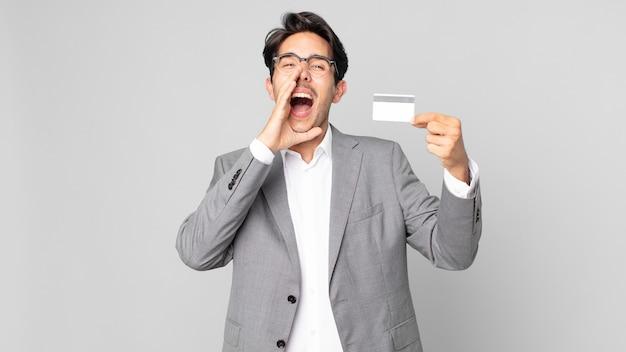 Jonge spaanse man die zich gelukkig voelt, een grote schreeuw geeft met de handen naast de mond en een creditcard vasthoudt