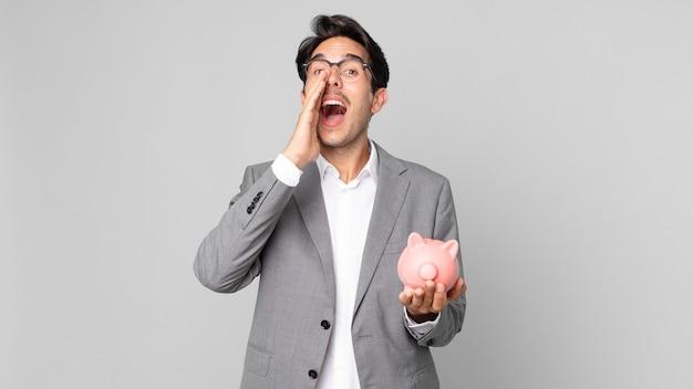 Jonge spaanse man die zich gelukkig voelt, een grote schreeuw geeft met de handen naast de mond en een spaarvarken vasthoudt