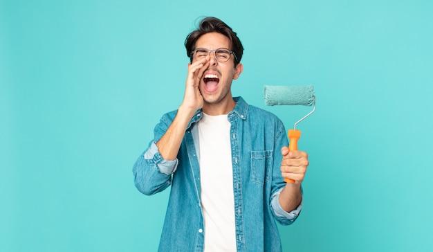 Jonge spaanse man die zich gelukkig voelt, een grote schreeuw geeft met de handen naast de mond en een verfroller vasthoudt