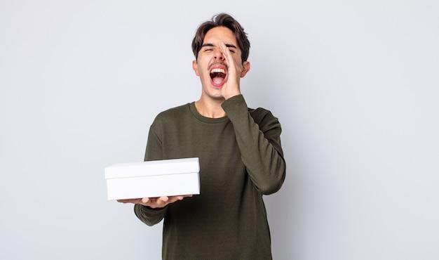 Jonge spaanse man die zich gelukkig voelt, een grote schreeuw geeft met de handen naast de mond. witte doos concept