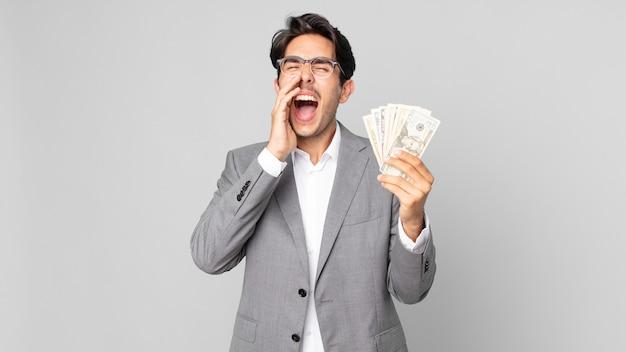 Jonge spaanse man die zich gelukkig voelt, een grote schreeuw geeft met de handen naast de mond