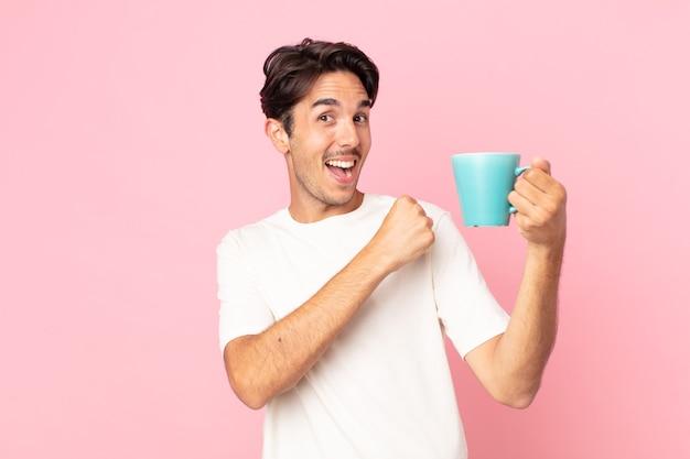 Jonge spaanse man die zich gelukkig voelt en een uitdaging aangaat of een koffiemok viert en vasthoudt