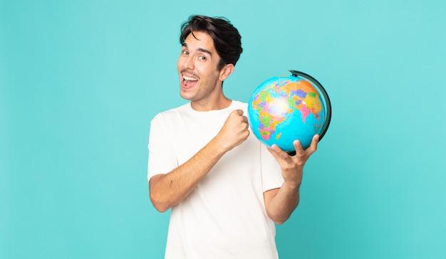 Jonge spaanse man die zich gelukkig voelt en een uitdaging aangaat of een wereldbolkaart viert en vasthoudt