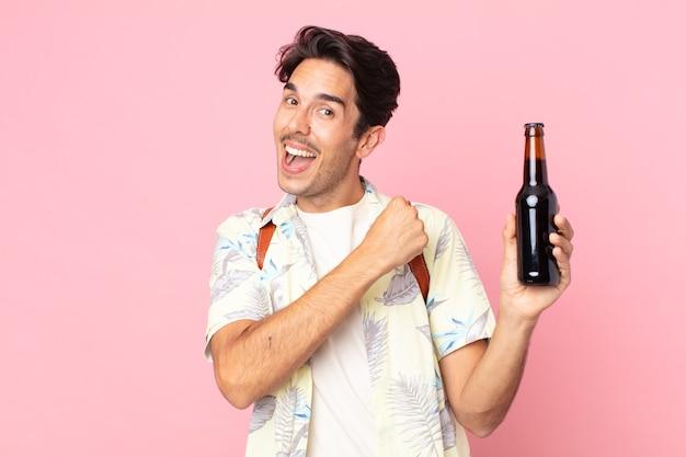Jonge spaanse man die zich gelukkig voelt en een uitdaging aangaat of viert en een flesje bier vasthoudt