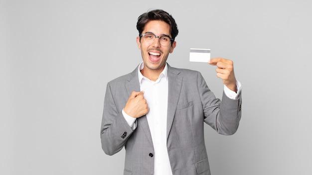 Jonge spaanse man die zich gelukkig voelt en naar zichzelf wijst met een opgewonden persoon en een creditcard vasthoudt