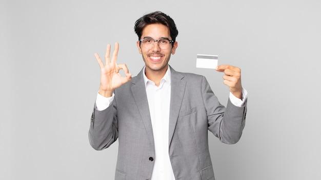 Jonge spaanse man die zich gelukkig voelt, goedkeuring toont met een goed gebaar en een creditcard vasthoudt