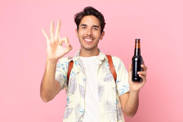 Jonge spaanse man die zich gelukkig voelt, goedkeuring toont met een goed gebaar en een flesje bier vasthoudt