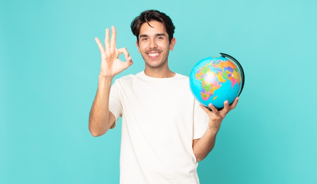 Jonge spaanse man die zich gelukkig voelt, goedkeuring toont met een goed gebaar en een wereldbolkaart vasthoudt