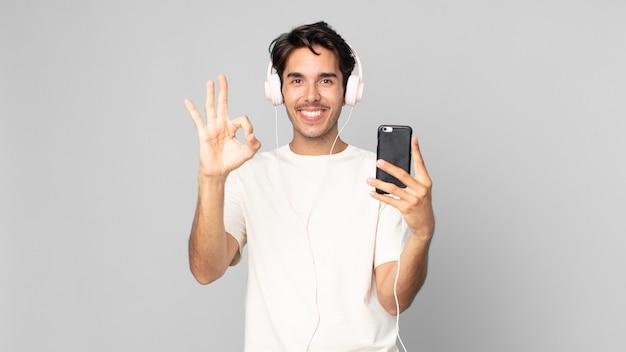 Jonge spaanse man die zich gelukkig voelt, goedkeuring toont met een goed gebaar met koptelefoon en smartphone