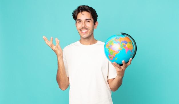 Jonge spaanse man die zich gelukkig voelt, verrast een oplossing of idee realiseert en een wereldbolkaart vasthoudt