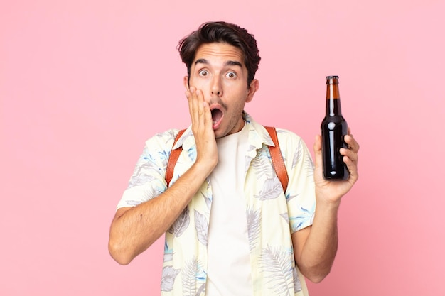 Jonge spaanse man die zich geschokt en bang voelt en een flesje bier vasthoudt