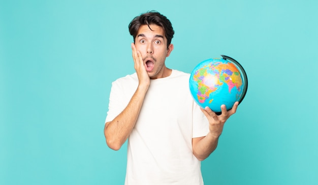 Jonge spaanse man die zich geschokt en bang voelt en een wereldbolkaart vasthoudt