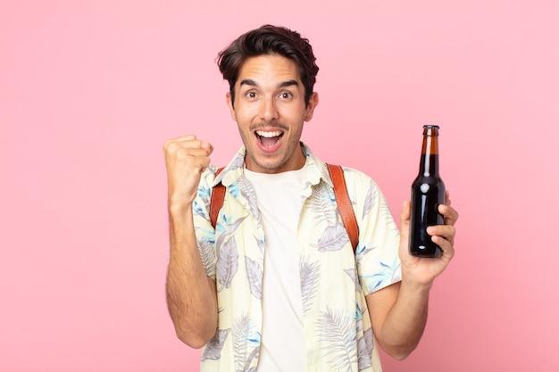 Jonge spaanse man die zich geschokt voelt, lacht en succes viert en een flesje bier vasthoudt