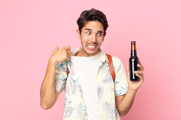 Jonge spaanse man die zich gestrest, angstig, moe en gefrustreerd voelt en een flesje bier vasthoudt