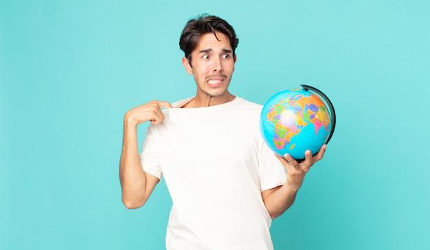 Jonge spaanse man die zich gestrest, angstig, moe en gefrustreerd voelt en een wereldbolkaart vasthoudt
