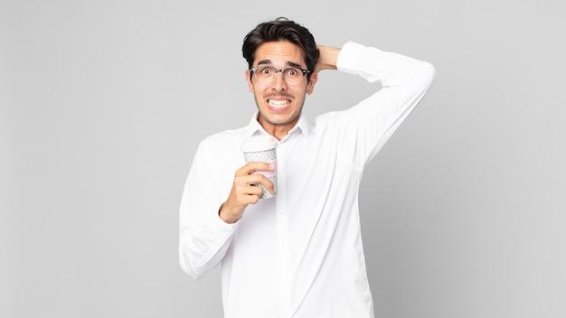 Jonge spaanse man die zich gestrest, angstig of bang voelt, met de handen op het hoofd en een afhaalkoffie vasthoudt