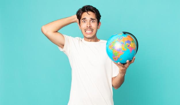 Jonge spaanse man die zich gestrest, angstig of bang voelt, met de handen op het hoofd en een wereldbolkaart vasthoudt