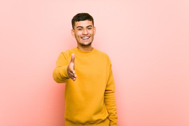 Jonge spaanse man die zich uitstrekt hand op camera in groet gebaar.
