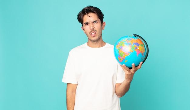 Jonge spaanse man die zich verbaasd en verward voelt en een wereldbolkaart vasthoudt