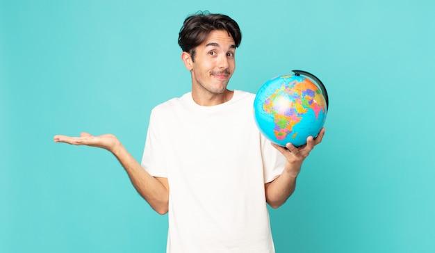 Jonge spaanse man die zich verbaasd en verward voelt en twijfelt en een wereldbolkaart vasthoudt