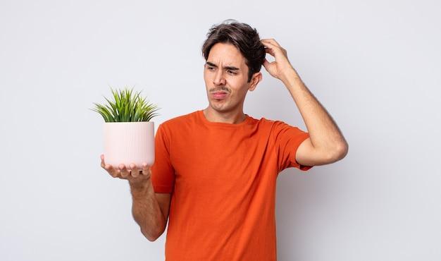 Jonge spaanse man die zich verbaasd en verward voelt, hoofd krabben. decoratief plantenconcept