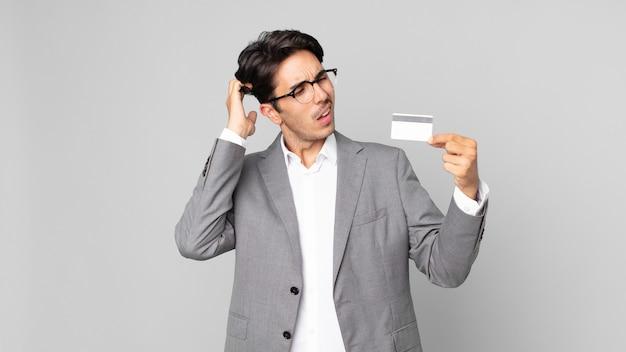 Jonge spaanse man die zich verbaasd en verward voelt, hoofd krabt en een creditcard vasthoudt