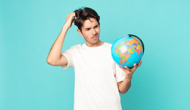 Jonge spaanse man die zich verbaasd en verward voelt, hoofd krabt en een wereldbolkaart vasthoudt