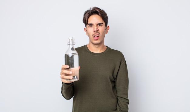 Jonge spaanse man die zich verbaasd en verward voelt. waterfles concept