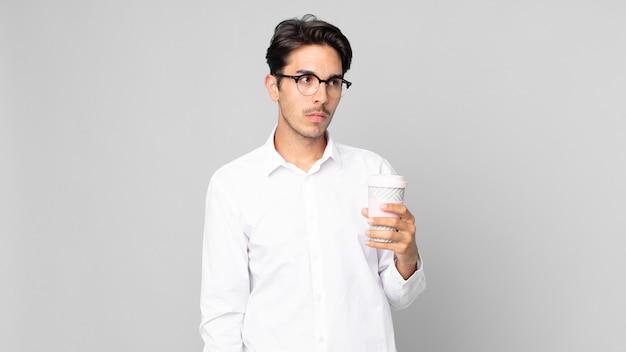 Jonge spaanse man die zich verdrietig, overstuur of boos voelt en opzij kijkt en een afhaalkoffie vasthoudt