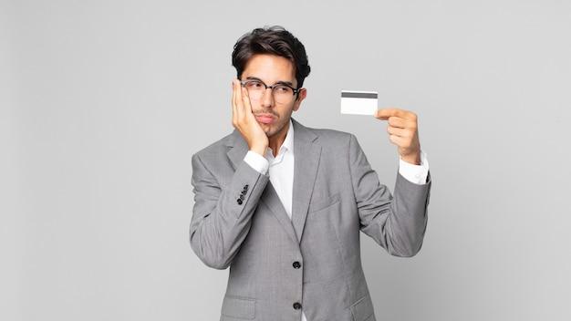 Jonge spaanse man die zich verveeld, gefrustreerd en slaperig voelt na een vermoeiende bezigheid en een creditcard vasthoudt