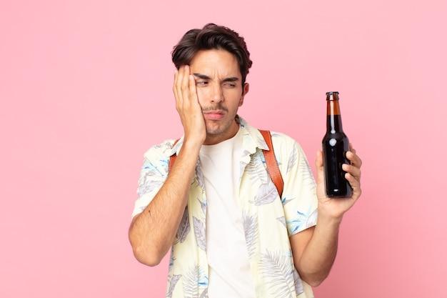 Jonge spaanse man die zich verveeld, gefrustreerd en slaperig voelt na een vermoeiende bezigheid en een flesje bier vasthoudt