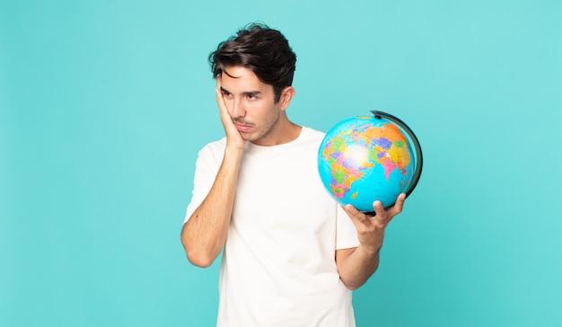 Jonge spaanse man die zich verveeld, gefrustreerd en slaperig voelt na een vermoeiende en een wereldbolkaart vast te houden