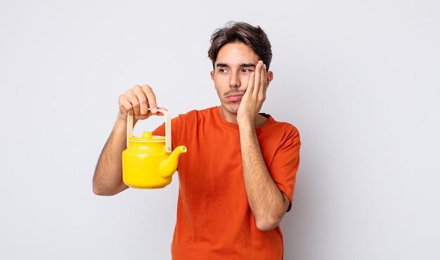 Jonge spaanse man die zich verveeld, gefrustreerd en slaperig voelt na een vermoeiende. theepot concept