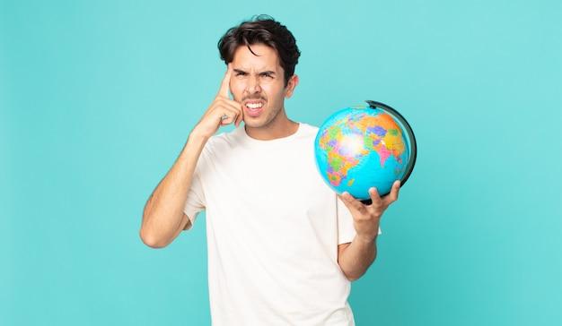 Jonge spaanse man die zich verward en verbaasd voelt, laat zien dat je gek bent en een wereldbolkaart vasthoudt