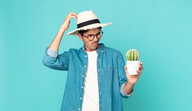 Jonge spaanse man die zich verward en verward voelt, hoofd krabt en een cactus vasthoudt