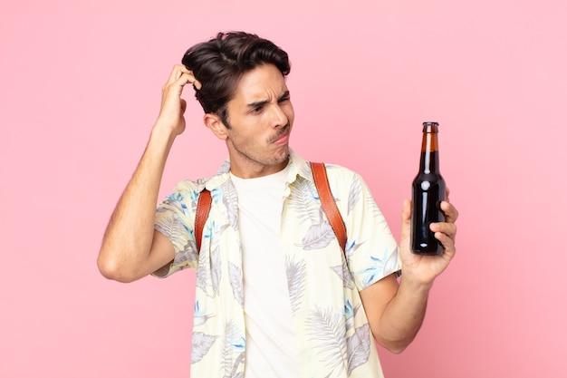 Jonge spaanse man die zich verward en verward voelt, hoofd krabt en een flesje bier vasthoudt