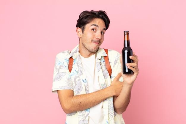 Jonge spaanse man die zijn schouders ophaalt, zich verward en onzeker voelt en een flesje bier vasthoudt