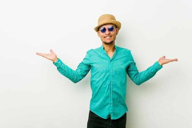 Jonge spaanse man draagt een zomer kleding maakt schaal met armen, voelt zich gelukkig en zelfverzekerd.