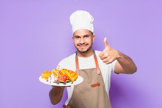 Jonge spaanse man gelukkig expressie. chef-kok met wafels concept