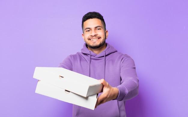 Jonge spaanse man gelukkige uitdrukking en afhaalpizza's vasthouden?