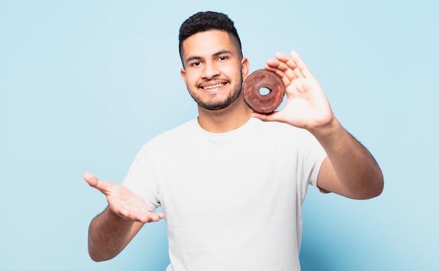 Jonge spaanse man gelukkige uitdrukking en met een donut